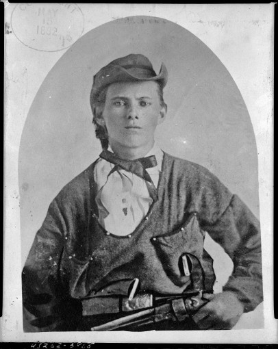 Jesse James, half-length portrait, facing front, holding handgun in left hand at his waist